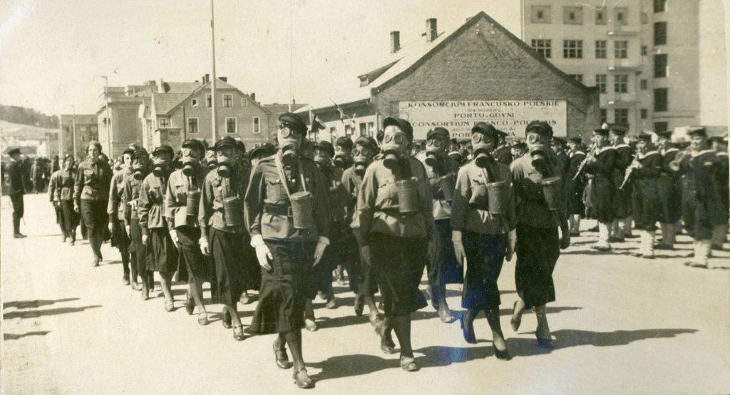kobiety w maskach gazowych podczas defilady
