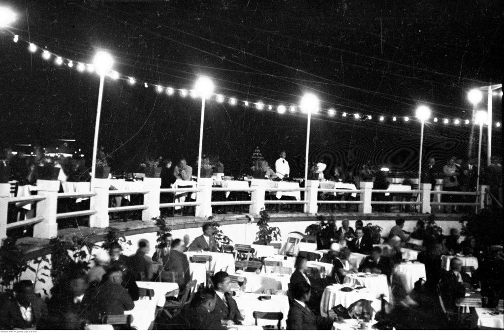ludzie przy stolikach nocą