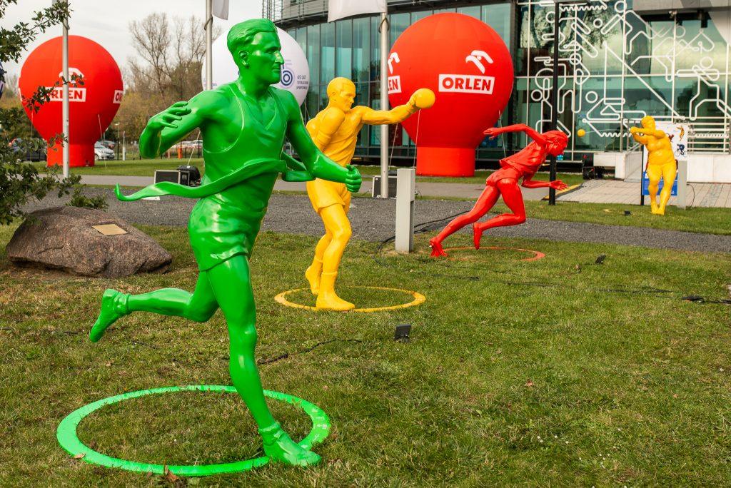 rzeźby na trawniku przed szklanym budynkiem PKOl