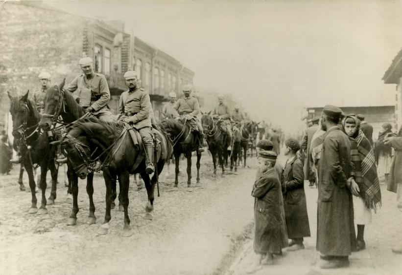 Czarno-białe zdjęcie przedstawiające Polskich Żydów obserwujących wjeżdżające do Parczewa wojska niemieckie