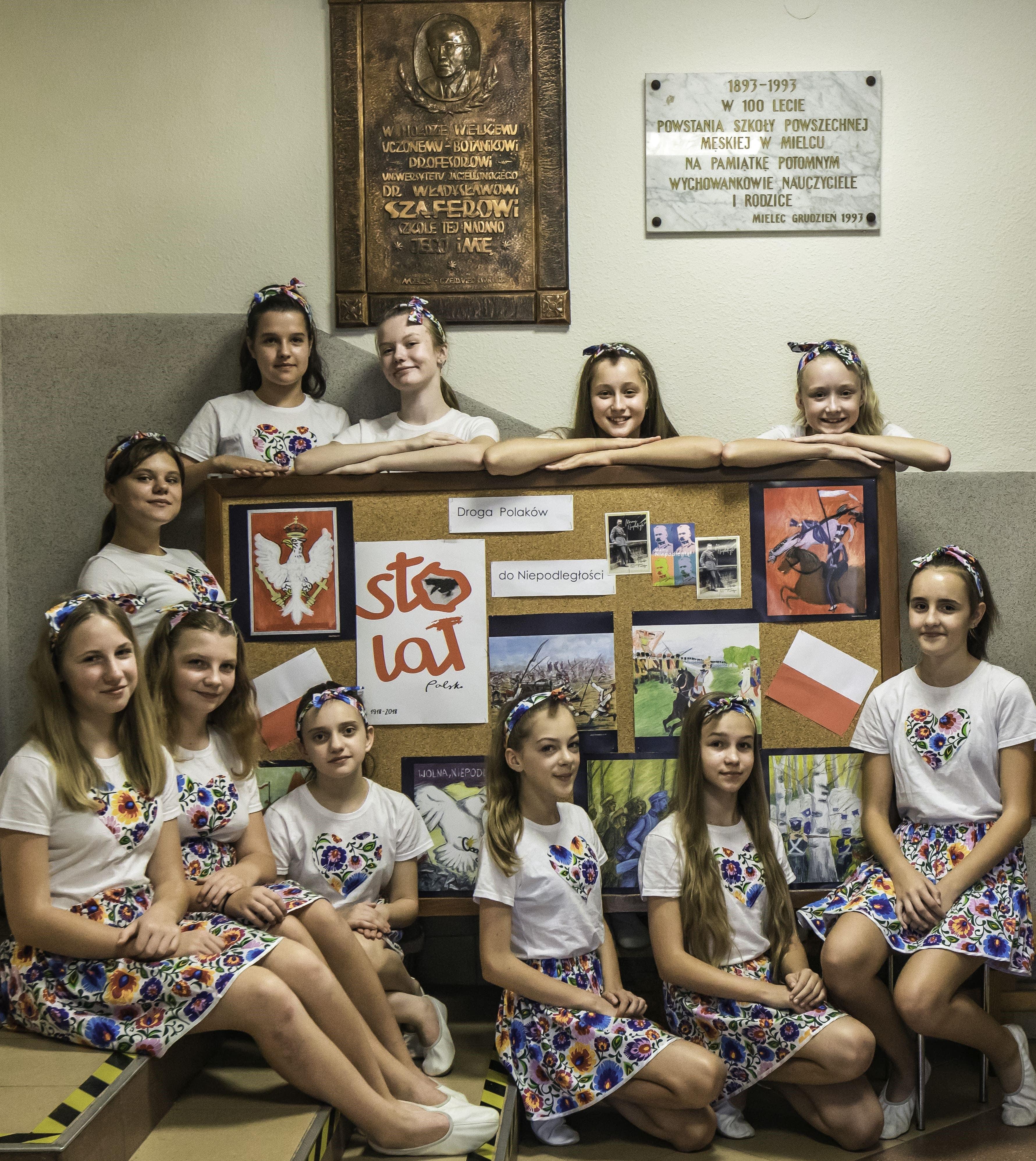 Zdjęcie przedstawia uczennice SP1 w Mielcu w strojach z motywami ludowymi prezentujące gazetkę