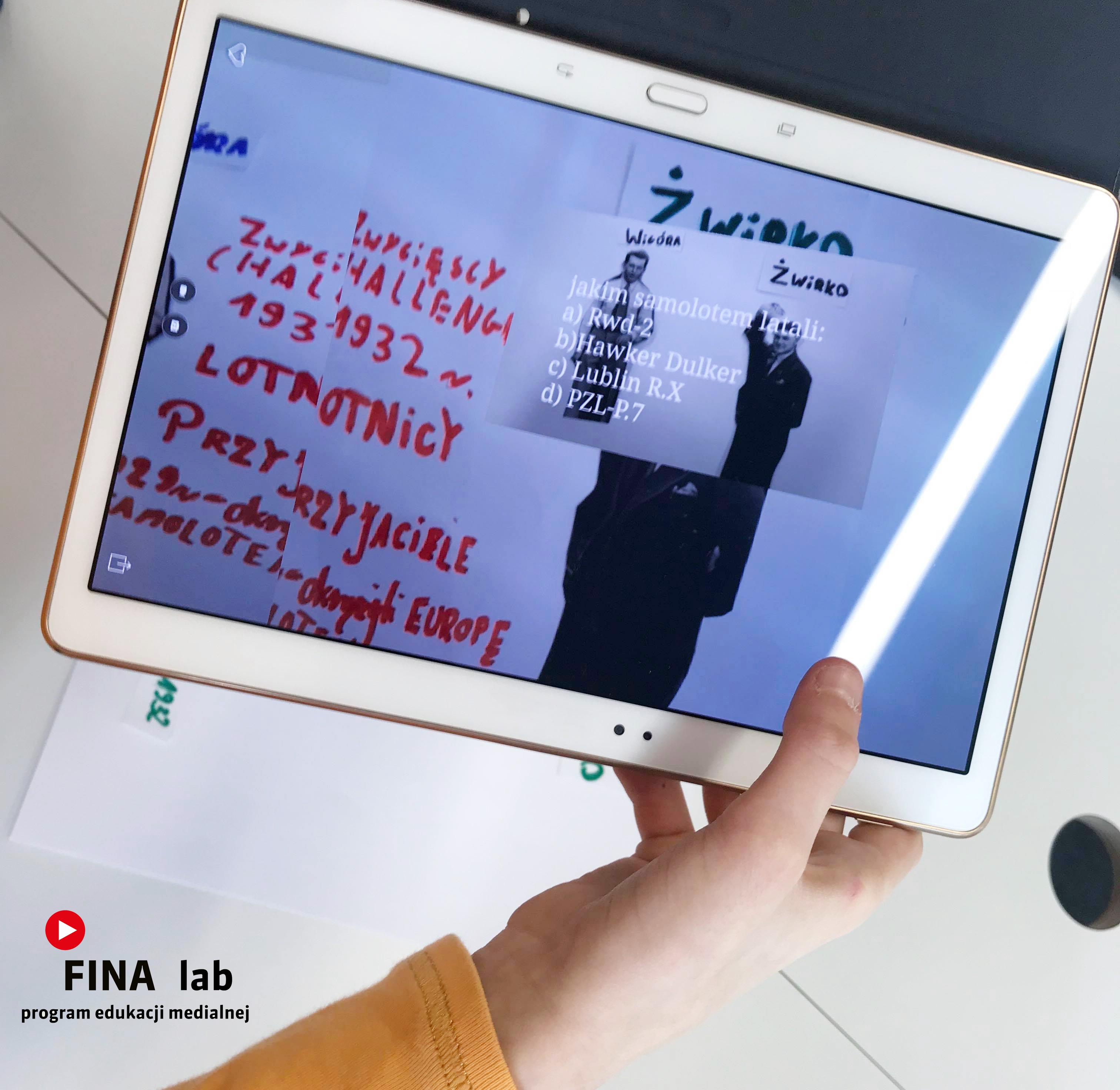 dłoń trzyma tablet ze zdjęciami, baner warsztatów