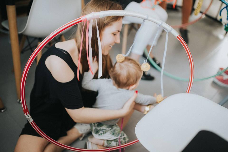 Zdjęcie wykonane podczas jednych z warsztatów dla małych dzieci. Przedstawia kobietę trzymającą na rękach małą dziewczynkę. Dziecko wygląda na wiek około 2 lat. Siedzi tyłem do osoby robiącej zdjęcie.
