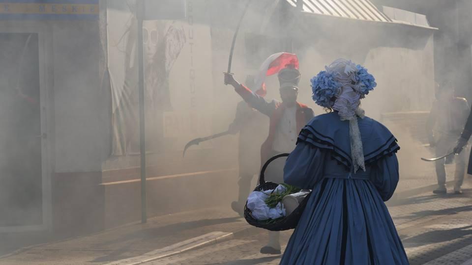 na pierwszym planie kobieta w xix-wiecznym stronu odwrócona tyłem obserwuje wkraczającego w chmurze dymu powstańca z uniesioną szablą