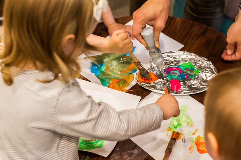 dziecko malujące pędzlem po kartce papieru
