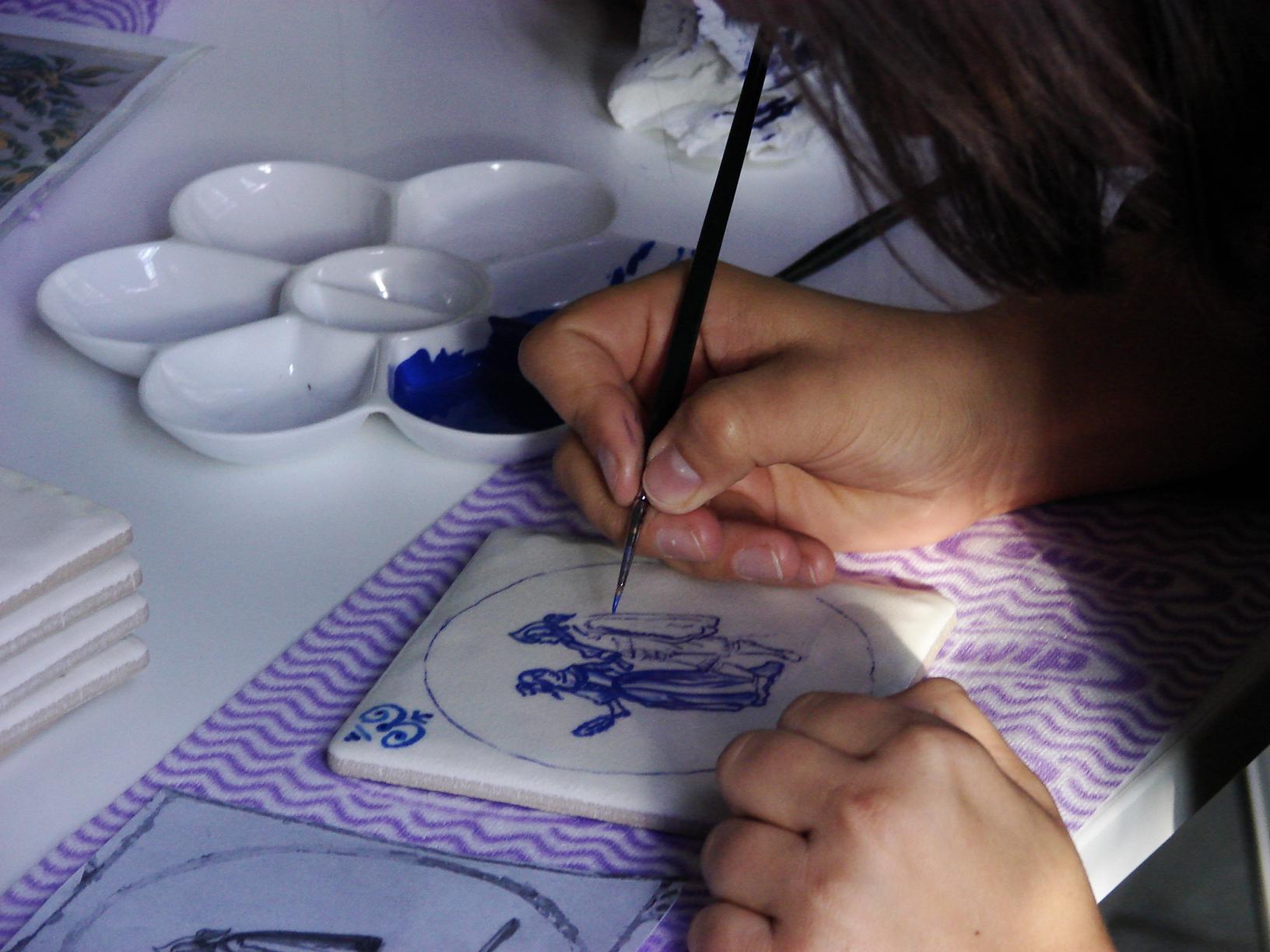 kobieta malująca pędzlem kobietę i mężczyznę na kawałku porcelany