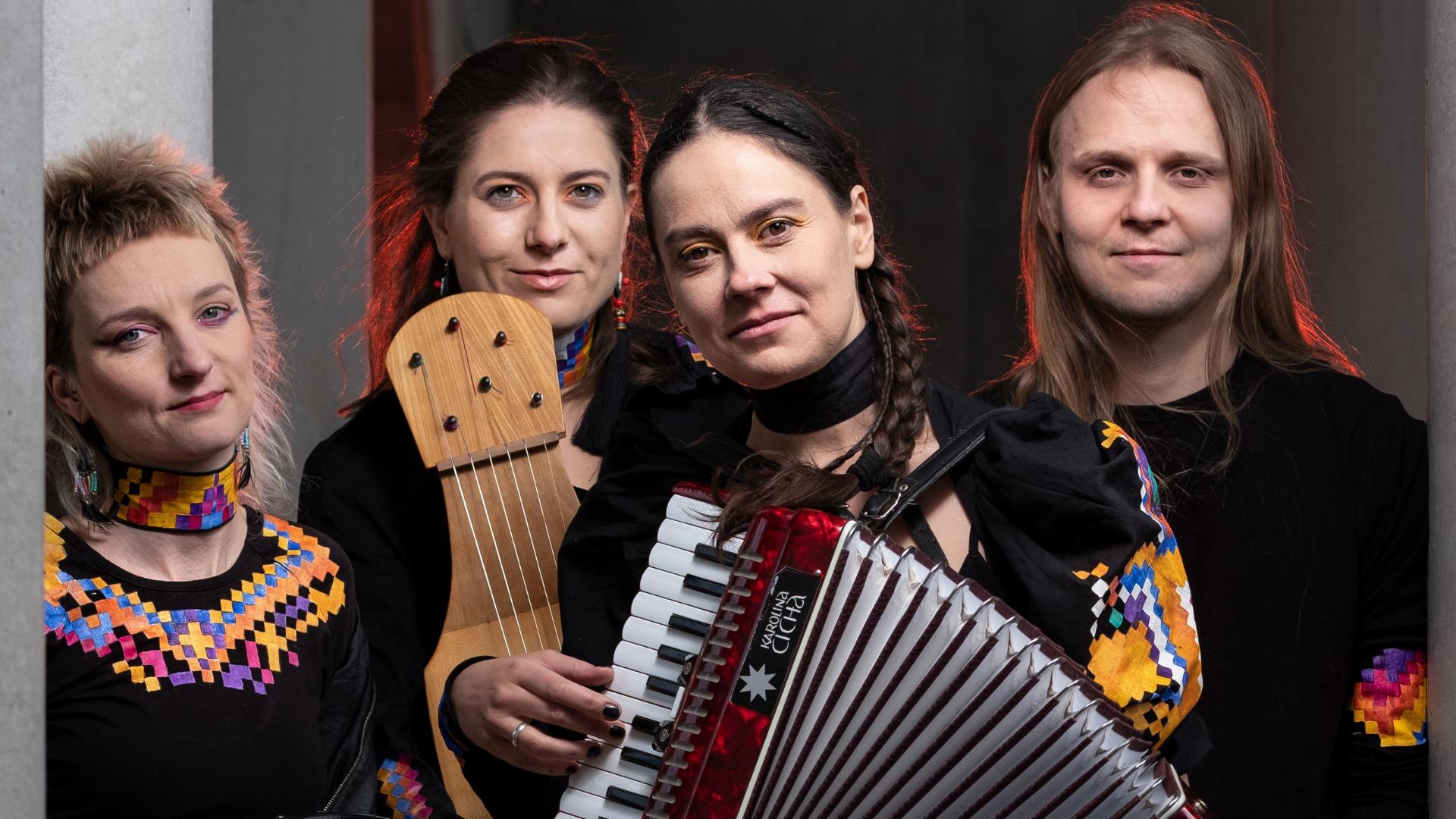 mężczyzna i trzy kobiety, z których dwie trzymają instrumenty