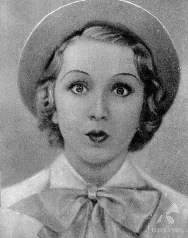 Zdziwiona kobieta z szeroko otwartymi oczami, ubrana w elegancką koszulę, nosząca kapelusz na głowie.