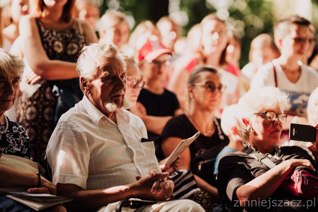 Grupa ludzi siedzących blisko siebie, uczestniczących w wydarzeniu kulturalno-artystycznym