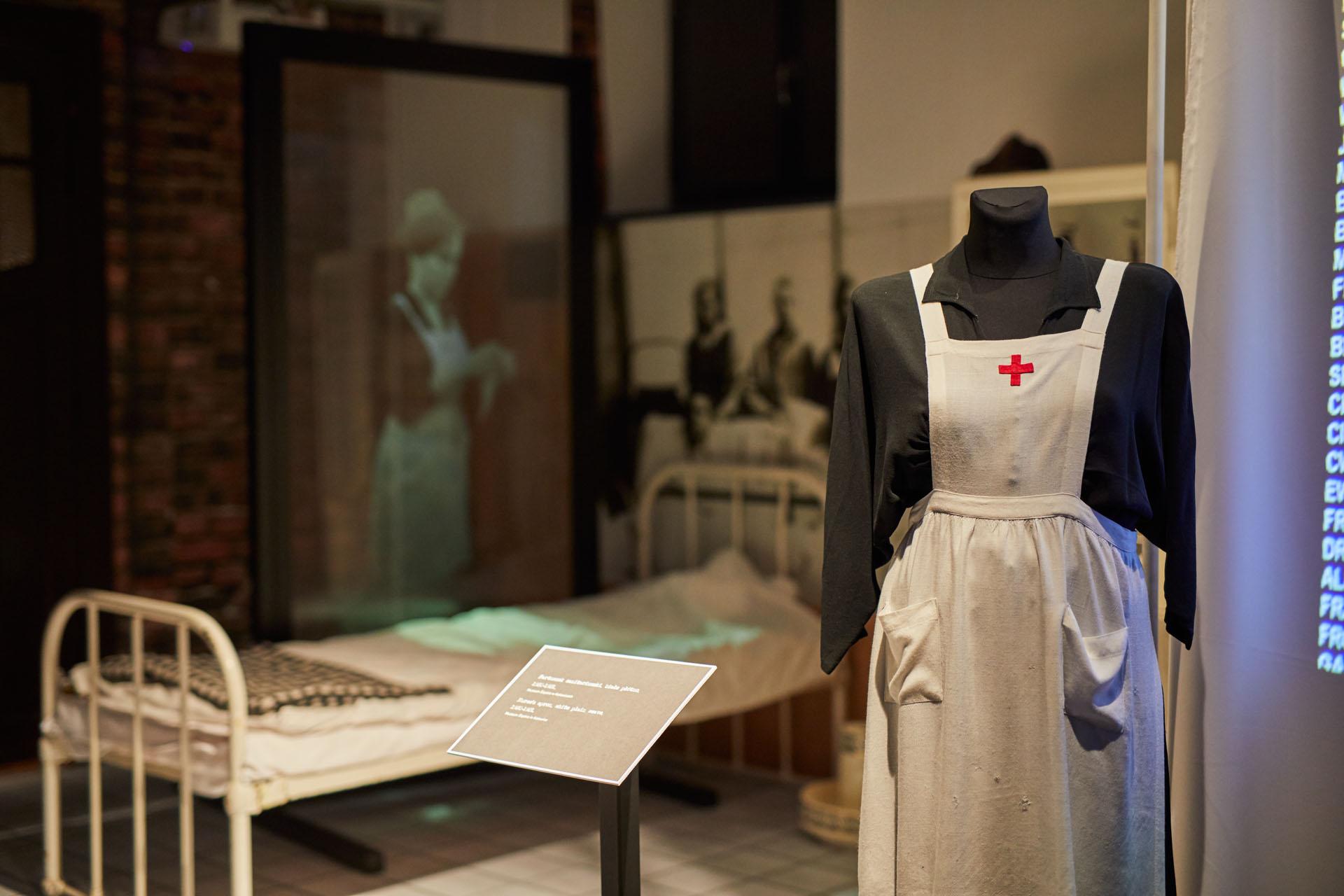 zdjęcie z wystawy, na pierwszym planie kukła ubrana w biały fartuch sanitariuszki z czerwonym krzyżem