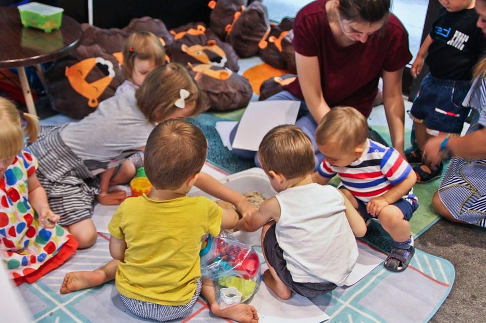 Grupa dzieci, malujących obrazy na kartkach papieru