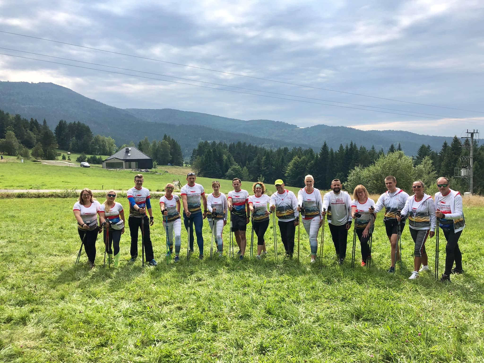 Grupa piętnastu kobiet i mężczyzn na tle gór. Stoją na polanie. Ubrani w sportową odzież. Kije do Nordic Walking trzymają w dłoniach.