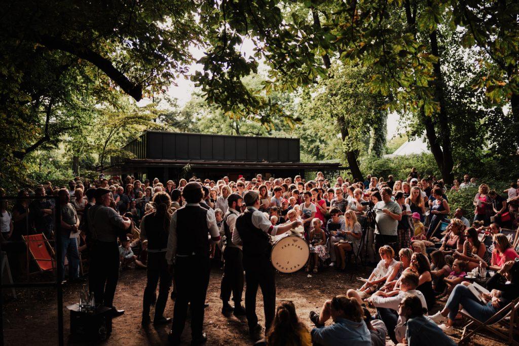 zdjęcie muzyków grających w parku przy kawiarni i tłum słuchaczy
