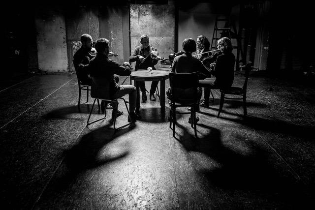 Na zdjęciu widać sześć siedzących osób, które grają na skrzypcach. Zdjęcie jest czarno - białe.