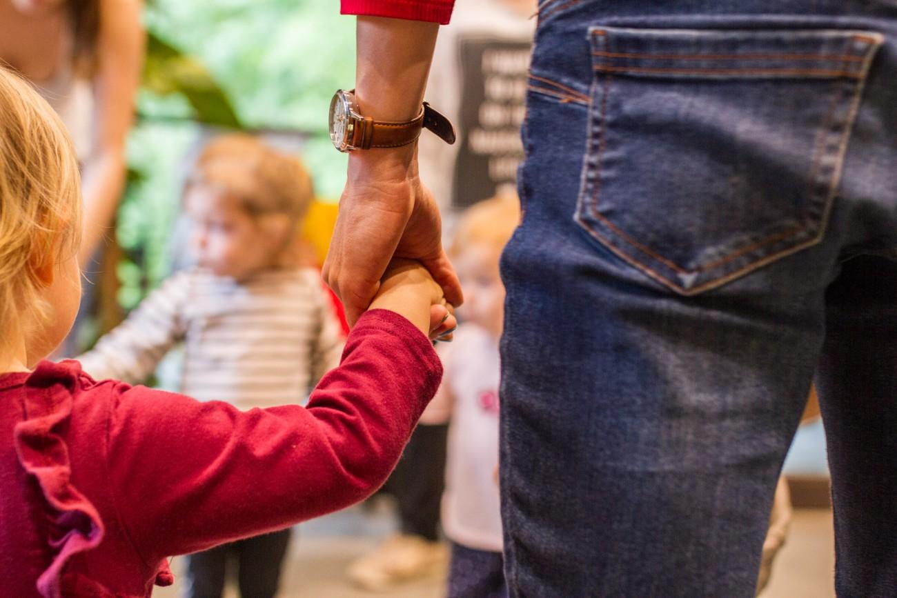 Zdjęcie przedstawia dziecko, trzymające za rękę osobę dorosłą. Kadr jest skoncentrowany na dłoniach. Tło rozmyte.