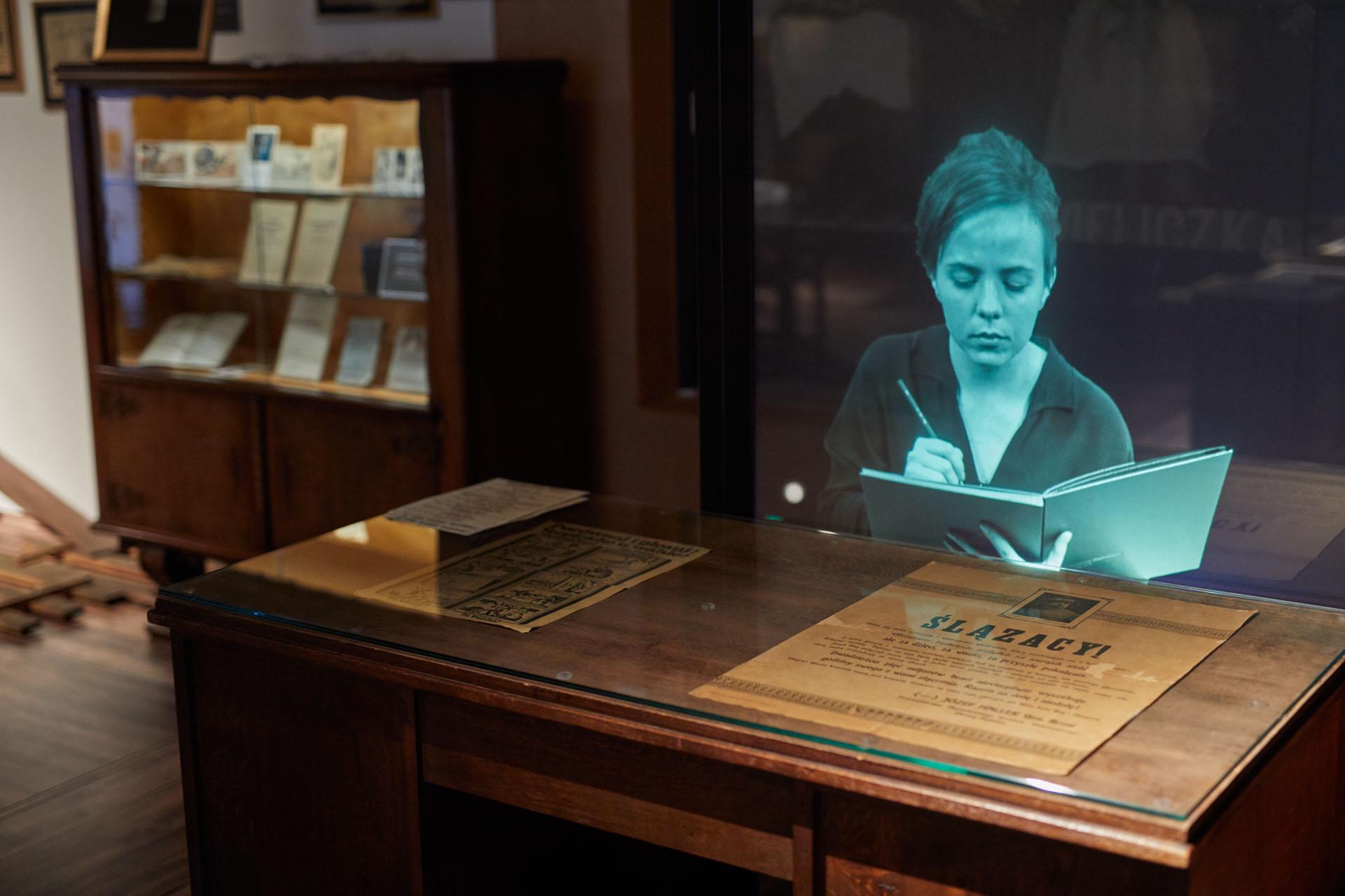 Widok na wystawę/. Widać biurko i eksponaty.