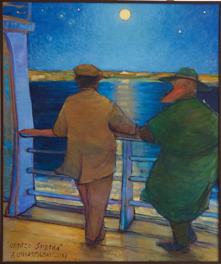 2 mężczyzn stojących tyłem do widza spoglądających z pokładu statku na wodę i horyzont