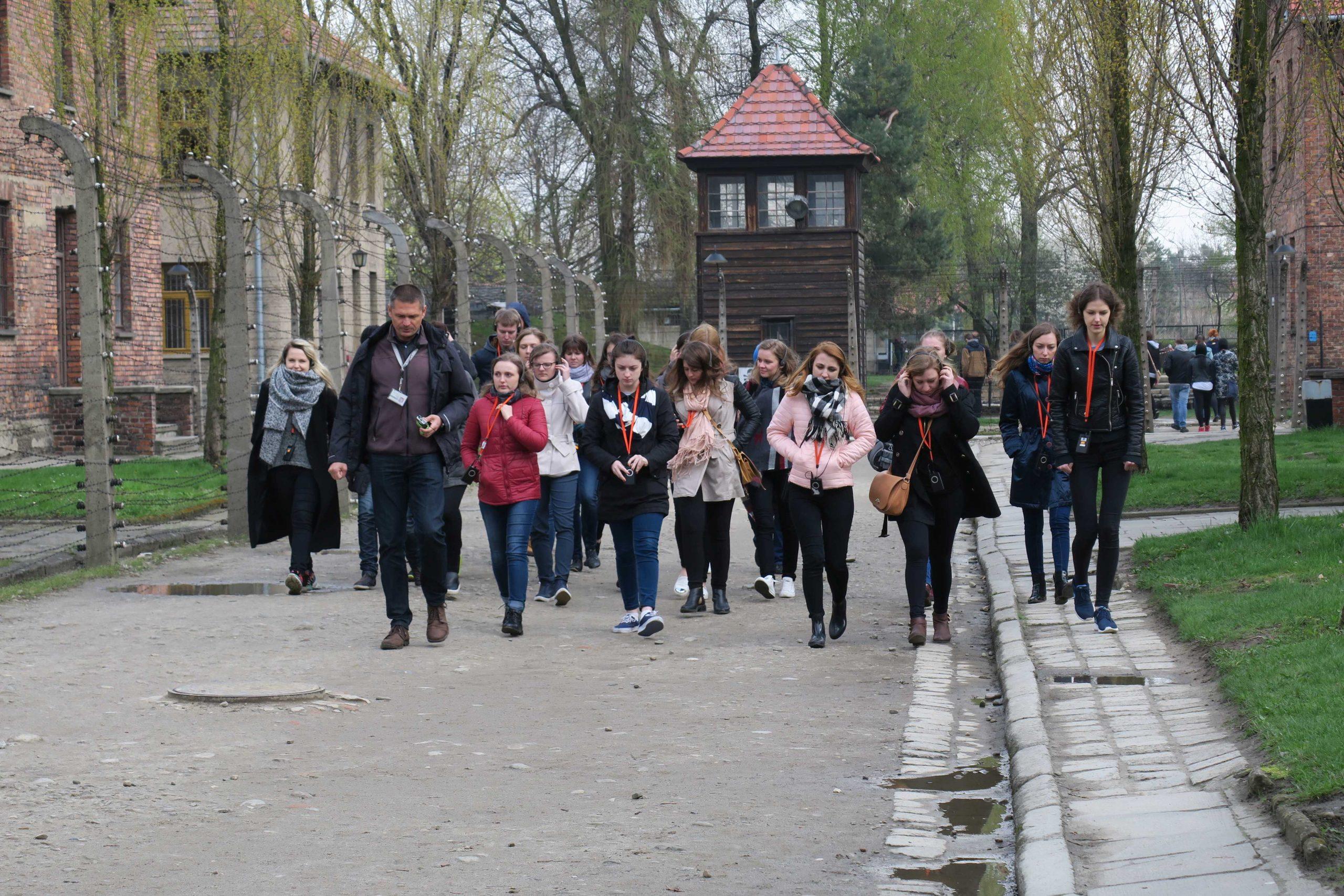 Grupa młodzieży zwiedzająca Miejsce Pamięci Auschwitz-Birkenau z przewodnikiem.