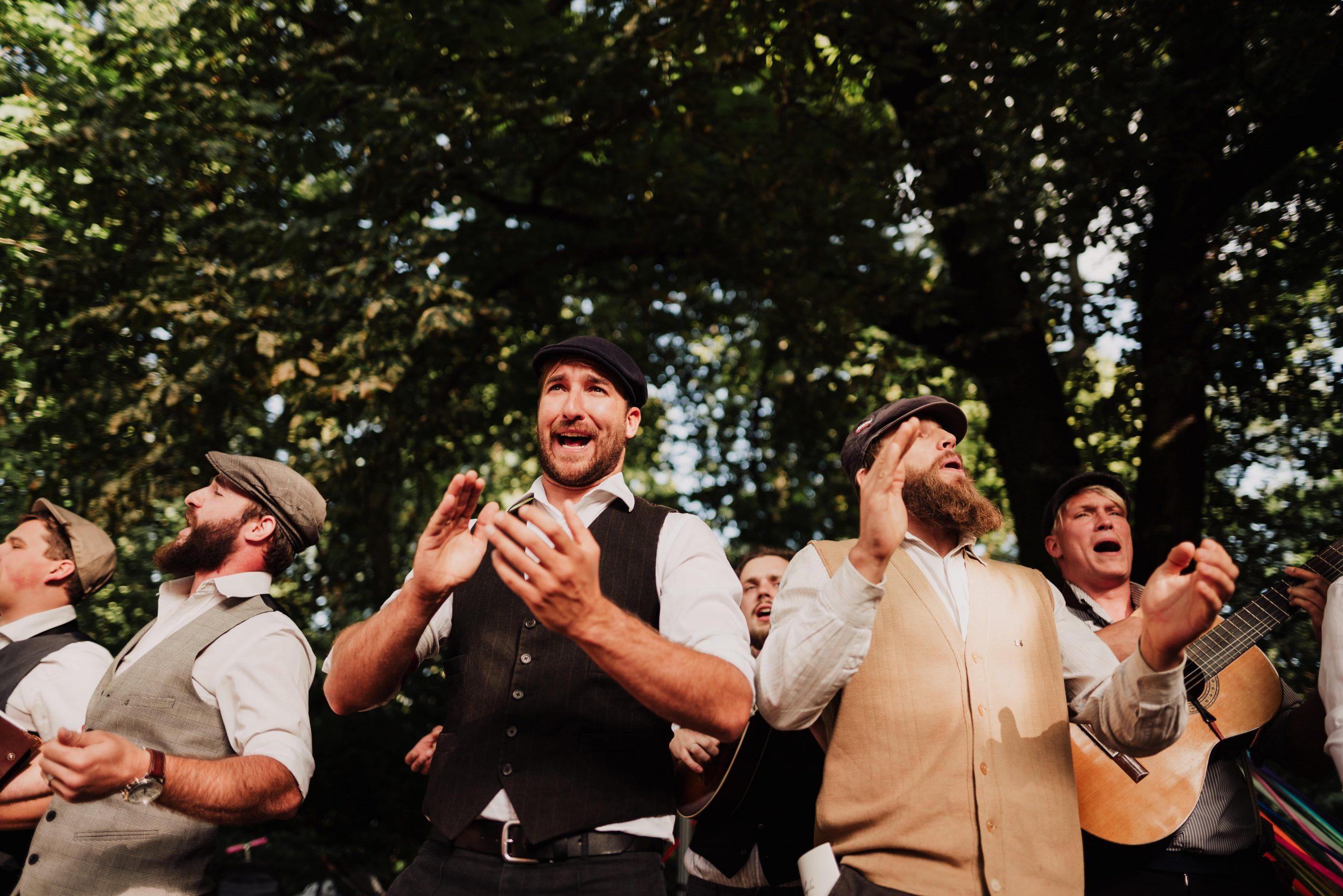 Na zdjęciu widać sześciu młodych mężczyzn, ubranych w białe koszule i kamizelki. Dwóch z nich gra na gitarze, pozostali klaszczą, wszyscy śpiewają. W tle widoczne są drzewa.
