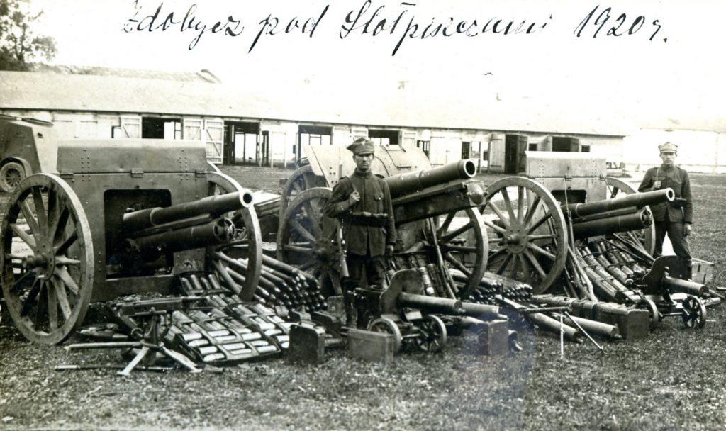 zdjęcie przedstawia żołnierzy 56 pułku piechoty Wielkopolskiej prezentujących zdobyte na bolszewikach w bitwie pod Stołpiszczem w dniu 4 czerwca 1920 r. armaty, ciężkie karabiny maszynowe i amunicję