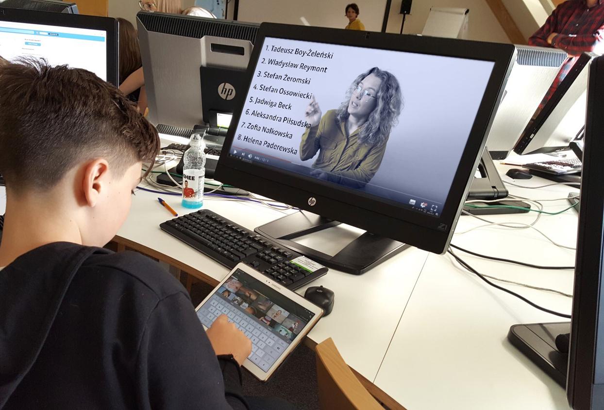 chłopiec siedzący przed komputerem z tabletem w  rękach