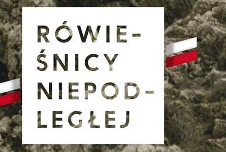 Ilustracja prostokątna w orientacji poziomej. Na tle ciemnobrązowego fragmentu zdjęcia, przedstawiającego kawałek skały, znajduje się biały kwadrat z brązowym napisem kapitalikami: Rówieśnicy Niepodległej. Po lewej i prawej stronie kwadratu znajdują się ukośne paski w kolorach polskiej flagi: biało-czerwonym.