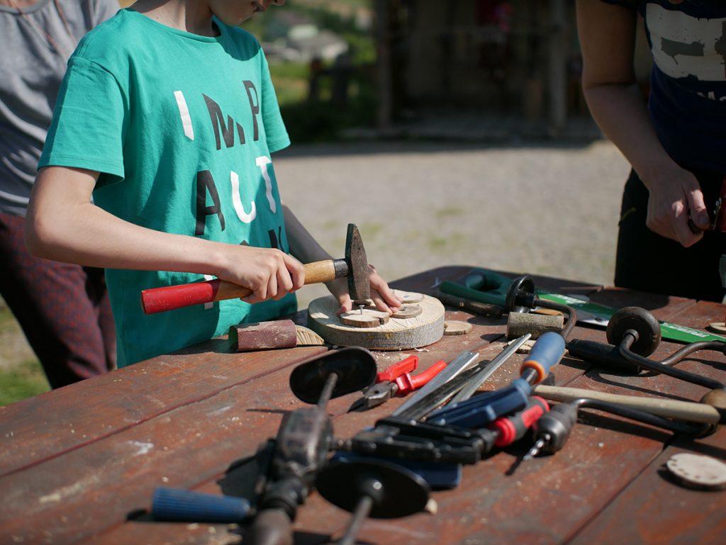 Dziecko pracujące przy drewnie z narzędziami stolarskimi
