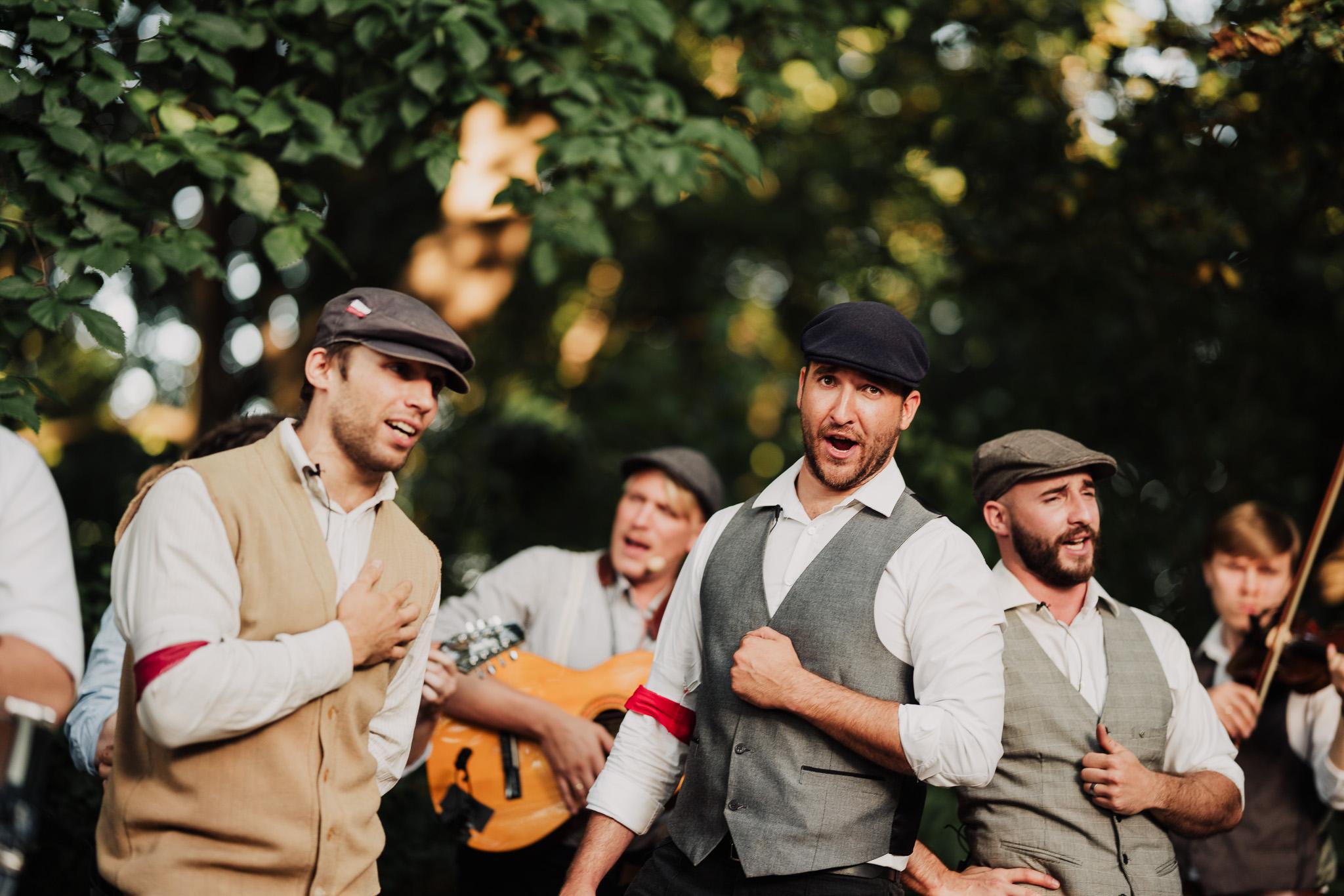 Mężczyźni w stokach z epoki śpiewają piosenkę