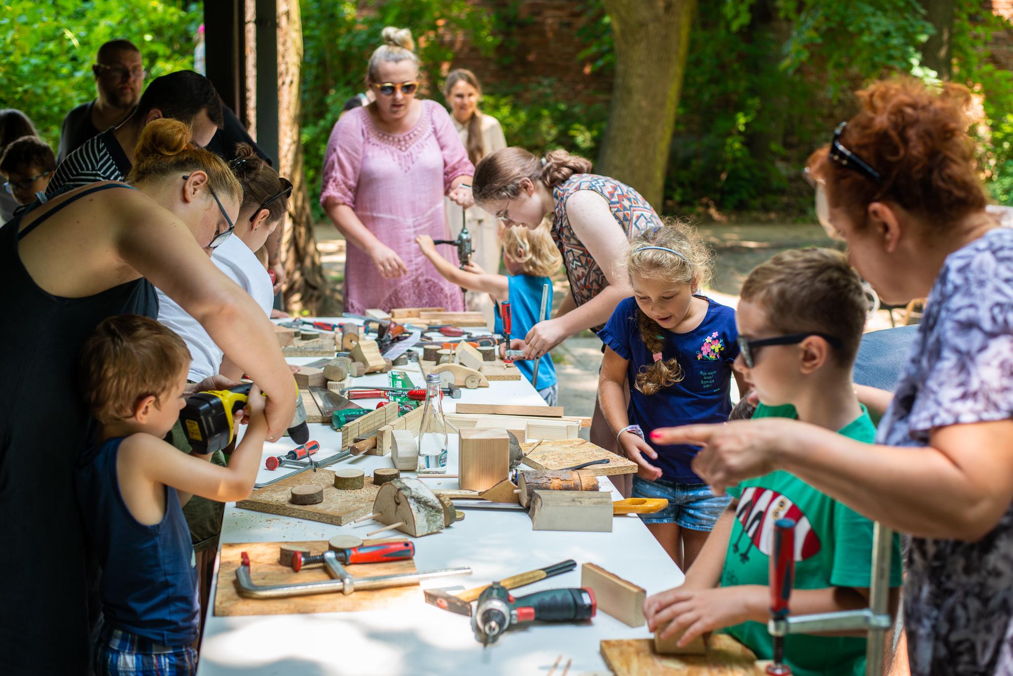 Grupa dorosłych i dzieci używająca narzędzi stolarskich