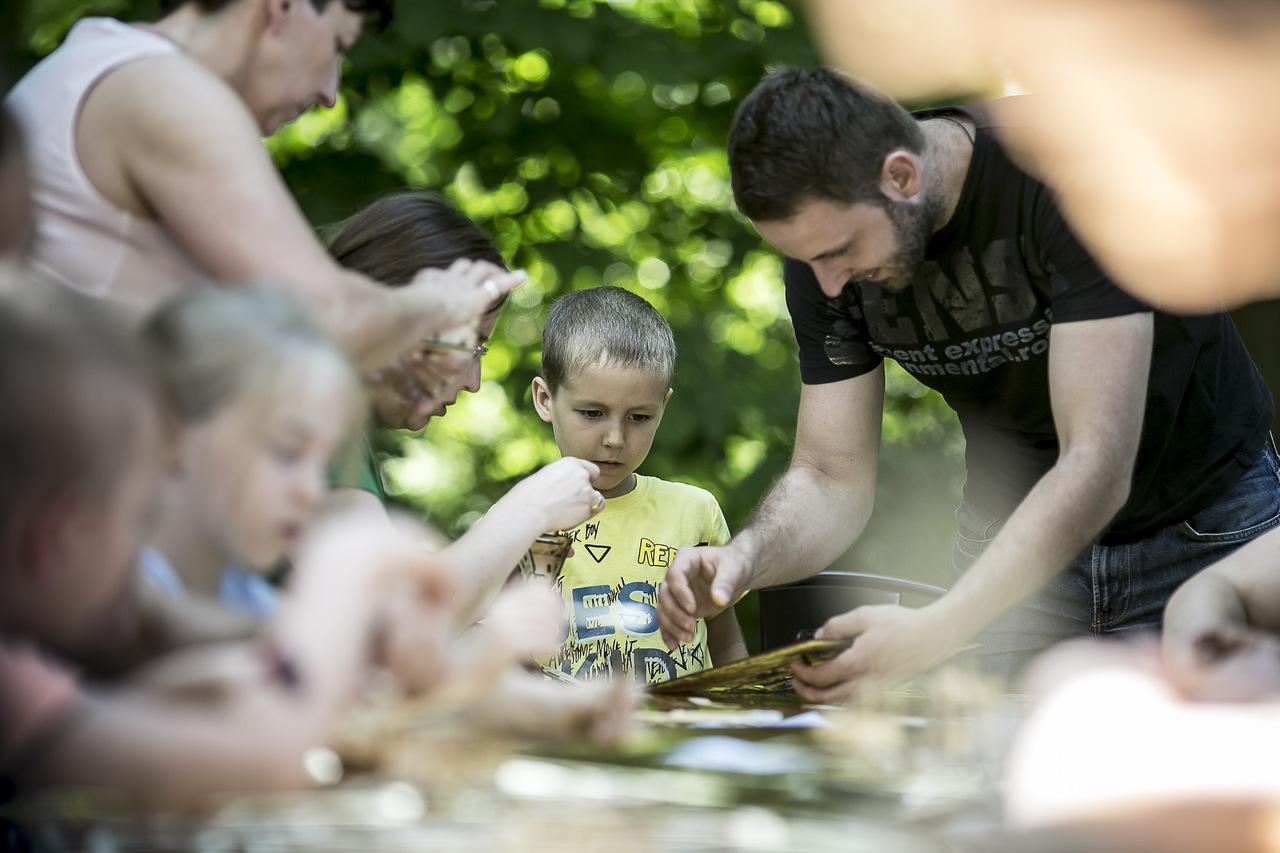 Zdjęcie przedstawia grupę dzieci i dorosłych siedzących przy długim stole, składających drewniane modele.