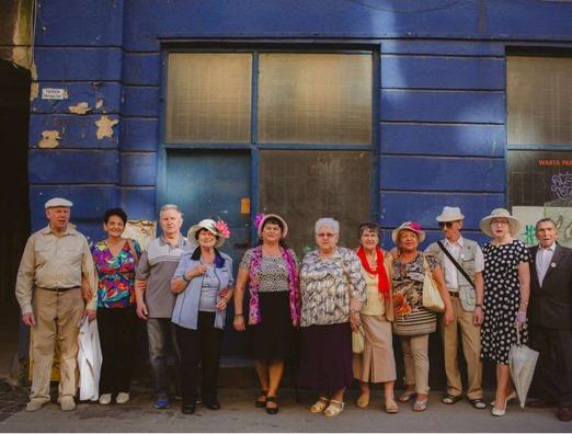 Na zdjęciu widać grupę jedenastu seniorów ubranych odświętnie, stojących na tle niebieskiej kamienicy.
