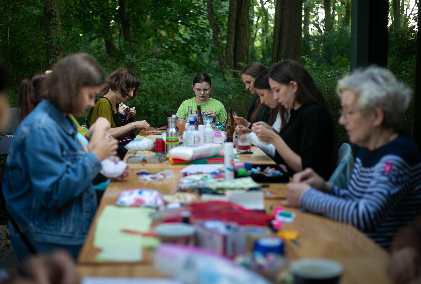 Zdjęcie przestawia kobiety w różnym wieku, siedzące przy długim stole w ogródku pawilonu Niepodległa. Miejsce spotkań. W dłoniach mają materiał i nawleczone igły. Na stole leżą guziki, nici i materiały niezbędne do przygotowania igielnika.
