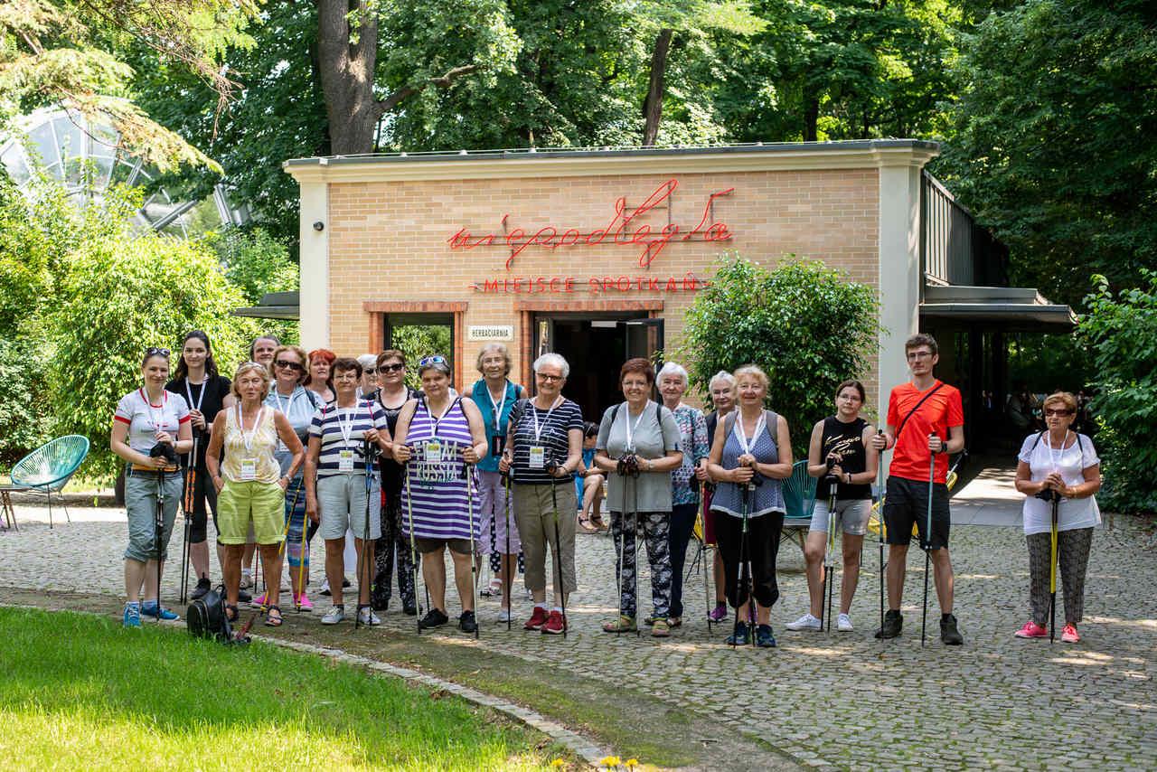 Zdjęcie przedstawia grupę uczestników warsztatów Nordic Walking stojących przed pawilonem Niepodległa. Miejsce spotkań.